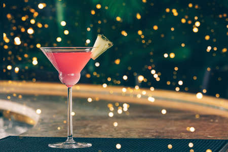 Cosmopolitan cocktail at the bar stand. Luxury vacation concept. Horizontal. Festive holiday celebration bokeh