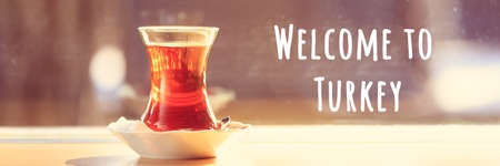 Hot turkish tea outdoors near glass wall. Turkish culture concept. Horizontal, banner format. Toned image, warm sunset light. Welcome to Turkey text Imagens