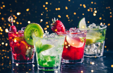 Four colorful tasty alcoholic cocktails in a row at the bar stand. Luxury vacation concept. Toned image. Festive holiday bokeh Imagens