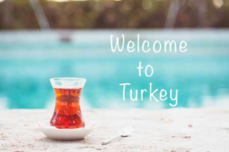 Hot turkish tea outdoors near water. Turkish tea and traditional turkish culture concept. Horizontal. Toned image. Welcome to Turkey text Imagens - 126500821