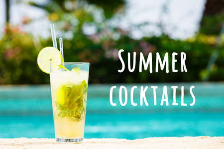 Mojito cocktail at the edge of a resort pool. Concept of luxury vacation. Outdoor pool background. Horizontal. Summer cocktails wording
