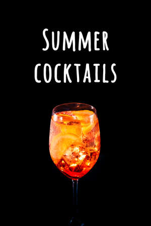 Stylish alcoholic trendy cocktail with orange slice on black background. Vertical photo. Summer cocktails wording