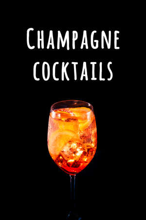 Stylish alcoholic trendy cocktail with orange slice on black background. Vertical photo.. Champagne cocktails wording Imagens