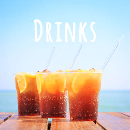 Concept of luxury tropical vacation. Cuba Libre or Long island ice tea cocktail on the pier. Beach party. Clear blue sky. Square. Drinks wording Фото со стока