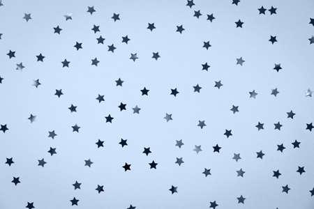 Star saupoudre sur fond de vacances festives solides dans une couleur saisonnière tendance. Concept de couleur et de célébration. Vue de dessus, mise à plat. Horizontal