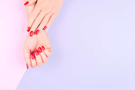 Woman hands with stylish red manicure on pastel lilac and pink background. Holiday, party and beauty concept. Horizontal Imagens