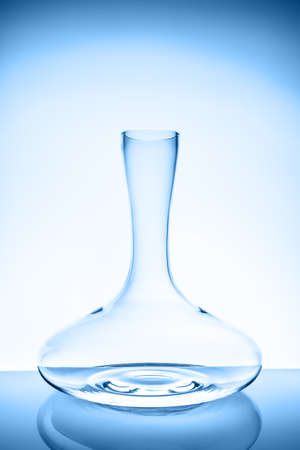 Luxury cristal decanter on the light background. Fine cristal glassware concept. Vertical toned in blue