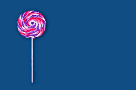Big lollipop on solid classic blue background. Horizontal