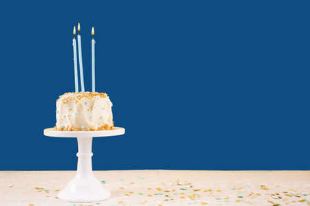 Birthday cake with candles on classic blue. Birthday party celebration concept. Horizontal, bold solid background 스톡 콘텐츠
