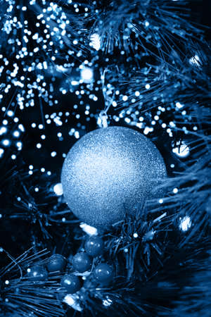 Seasonal background with Christmas toy on the tree toned in classic blue. Celebration concept. Soft focus. Vertical 版權商用圖片