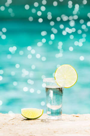One tequila shots with sliced lime on the beach. Transparent alcohol. Hanging out. Vertical with gentle festive holiday bokeh Imagens