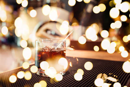 Black russian cocktail on the bar stand on rubber mat. Shallow DOF and marsala tonned with festive bokeh lights Stock Photo