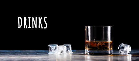 Glass of whiskey on the rocks with some ice on the table. Concept of hard liquor. Horizontal, wide screen banner format, isolated on black with Drinks wording