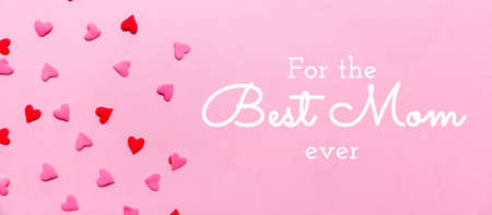 For the Best Mom ever wording and two tone heart sprinkles on the solid pink background. Romance, love, Valentines and mothers day concept. Flat lay, horizontal wide screen banner format