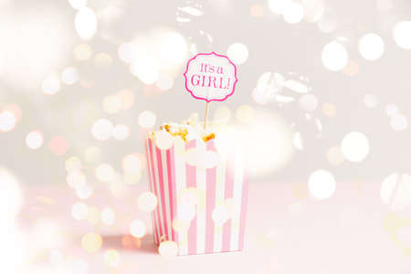 Its a girl sign in a popcorn bag at the baby shower party. Empty minimalistic party background. Baby shower celebration concept. Horizontal with festive holiday bokeh