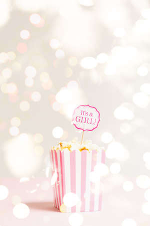 Its a girl sign in a popcorn bag at the baby shower party. Empty minimalistic party background. Baby shower celebration concept. Vertical with festive holiday bokeh