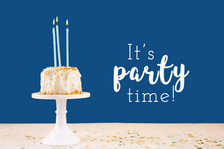 Birthday cake with candles on classic blue with It's party time wording. Birthday party celebration concept. Horizontal, bold solid background