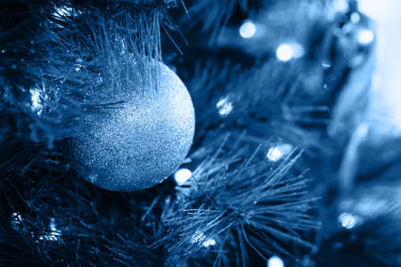 Seasonal background with Christmas toy on the tree toned in classic blue. Celebration concept. Soft focus. Horizontal
