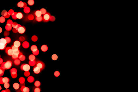 Black background with bright red warm bokeh lights. Holiday, Valentines, Christmas and New Year background. Ideal to layer with any design. Horizontal 免版税图像
