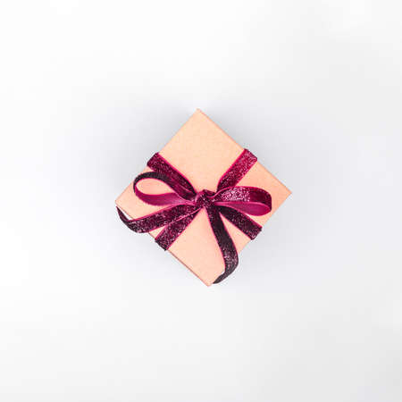 Craft boxes with dark red ribbon bows. Holiday, Christmas, New Year and Valentine day eco-friendly wrapping concept. Trendy minimalistic flat lay design background. Square