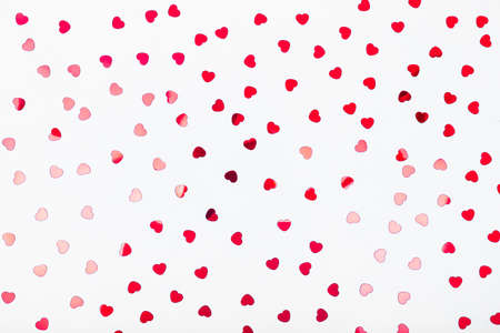 Grey background with red glitter heart confetti. Valentine day concept. Trendy minimalistic flat lay design background. Horizontal
