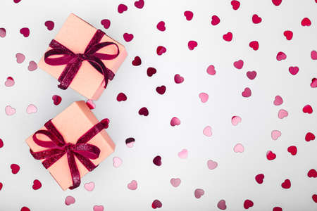 Craft box with dark red velvet ribbon bow and glitter heart confetti. Valentine day and eco-friendly wrapping concept. Trendy minimalistic flat lay design background. Horizontal 版權商用圖片