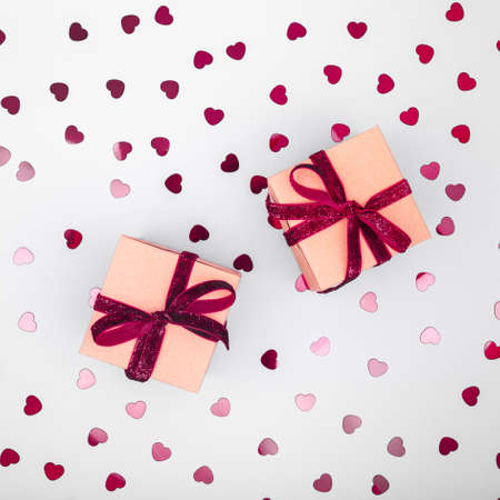 Craft box with dark red velvet ribbon bow and glitter heart confetti. Valentine day and eco-friendly wrapping concept. Trendy minimalistic flat lay design background. Square 版權商用圖片