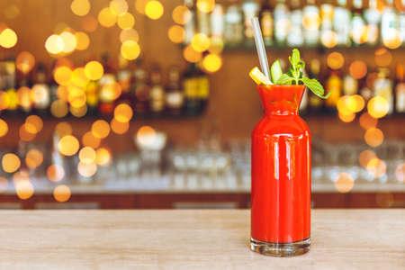 Cocktail classico Bloody Mary al bancone del bar con sfondo sfocato della barra. Posto per il testo. con effetto luci bokeh festivo Archivio Fotografico