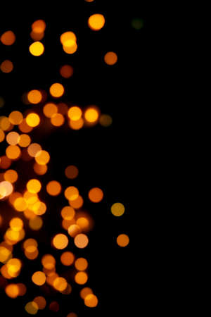 Black background with bright warm bokeh lights. Holiday, Christmas and New Year background. Ideal to layer with any design. Horizontal