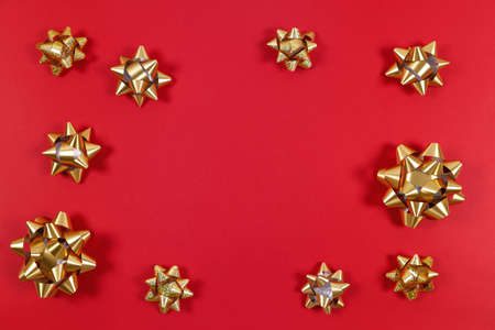 Golden gift bows on the red background. Traditional celebration and gift giving concept Foto de archivo - 140000730