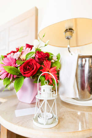 Lighthouse candle holder with champagne bottle and flower basket in the upscale hotel room. Being alone, getaway, staycation, digital detox, summer vacation concepts. Vertical Foto de archivo - 140000736
