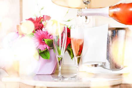 Pouring champagne into glasses in the upscale hotel room. Dating, romance, honeymoon, valentine, getaway concepts. Horizontal, light festive bokeh Foto de archivo - 140000738