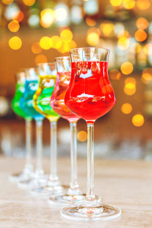 Many colorful tasty creative alcoholic cocktails in a row on bar stand. Luxury vacation concept. with festive bokeh lights effect Banco de Imagens