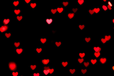 Black background with bright red warm heart shaped bokeh lights. Holiday, Valentines Day background. Ideal to layer with any design. Horizontal Banco de Imagens