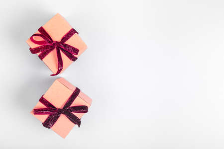 Craft boxes with dark red ribbon bows. Holiday, Christmas, New Year and Valentine day eco-friendly wrapping concept. Trendy minimalistic flat lay design background. Horizontal