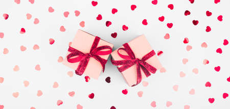 Craft box with red ribbon bow and glitter heart confetti. Valentine day and eco-friendly wrapping concept. Trendy minimalistic flat lay design background. Wide screen banner format Banco de Imagens