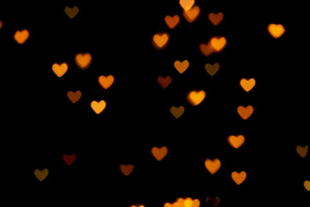 Black background with bright warm heart shaped bokeh lights. Holiday, Valentines Day background. Ideal to layer with any design. Horizontal Banco de Imagens