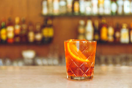 Glass of tasty alcoholic negroni cocktail with orange slice on bar stand. Festive concept. Banco de Imagens