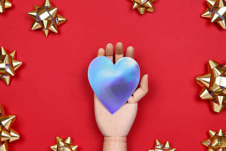 Futuristic image with a robot hand holding silver metal holographic heart on red drop with golden star bows. Robotic, ai, science, connection, technology, humanity concepts Zdjęcie Seryjne