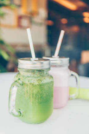 Healthy smoothie options in eco friendly glass jars with paper straws and light dumbbels in a luxury gym recreation area or vegan cafe. Trendy muted toning, place for text Banco de Imagens