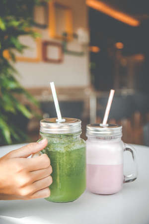 Woman hand holding healthy smoothie in eco friendly glass jar with paper straws in a luxury gym recreation area or vegan cafe. Trendy muted toning, place for text Banco de Imagens