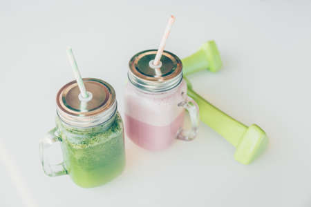 Healthy smoothie options in eco friendly glass jars with paper straws and light dumbbels in a luxury gym recreation area or vegan cafe. Trendy muted toning, place for text
