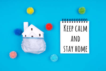 Cute little house covered with medicine mask and plastic balls aka viruses on the blue with Keep calm and stay home wording. Epidemic, social isolation, coronavirus COVID-19 concept. Option with text