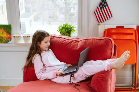 Preteen girl enjoyes homeschooling in comfy pijama and cozy sofa chair. Remote education, virus protection, social distancing and lockdown concept. household items at the back Foto de archivo