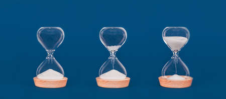 Hourglasses with increasing amount of sand. Concept of time and timely actions, time management and growth mindset. Banner format