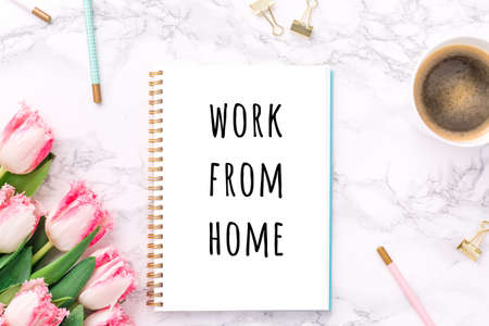Pink tulips with festive stationary and coffee on white marble background with Work from home wording. Feminine job, gender equality, home office and career concept. Copy space Top view. Horizontal Stock Photo