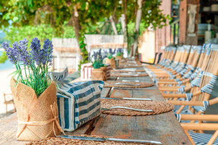 Empty tables ready for guests at the beach restaurant and bar near the sea. Vacation, get away, summer outing, crisis, lockdown concept Foto de archivo