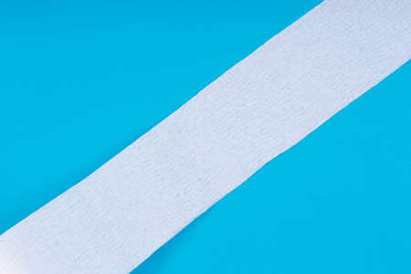 Toilet paper roll on the bright blue background. Coronavirus COVID-19 pandemic panic shopping, social distancing concept. Bright monochrome drop with diagonal line and place for text