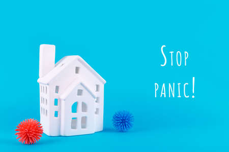 Cute little house and plastic balls as viruses on blue with Stop panic wording. Epidemic, social isolation, coronavirus COVID-19 concept. Option with text