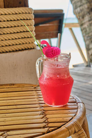 Colorful watermelon mocktail on straw table at the beach bar. Vacation, get away, summer outing concept